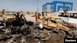 People gather at the site of car bomb attack in Baghdad, May 13, 2014.