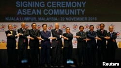Laos' Prime Minister Thongsing Thammavong, in the middle of Asean leaders as they join their hands to pose for photographers after the signing ceremony of the 2015 Kuala Lumpur Declaration on the Establishment of the Association of Southeast Asian Nations (ASEAN) Community and the Kuala Lumpur Declaration on ASEAN 2025, in Kuala Lumpur, Malaysia, Sunday, Nov. 22, 2015. (AP Photo/Lai Seng Sin)