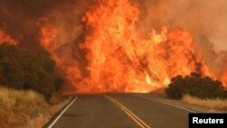 Bright flames are seen on a road in Mariposa County, California, July 17, 2017 in this picture obtained from social media.