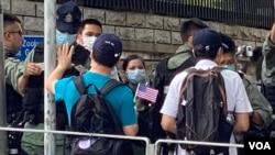 香港市民李先生手持小型的紙製美國國旗,與多名朋友7月4日下午到美國駐港總領事館附近慶祝美國國慶,他們被大批警員截查。(美國之音 湯惠芸拍攝)