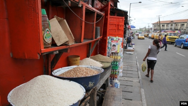 Local and imported rice is sold from bowls in front of a shop in Obalende market in Lagos, Nigeria, March 3, 2016. (C. Stein/VOA)