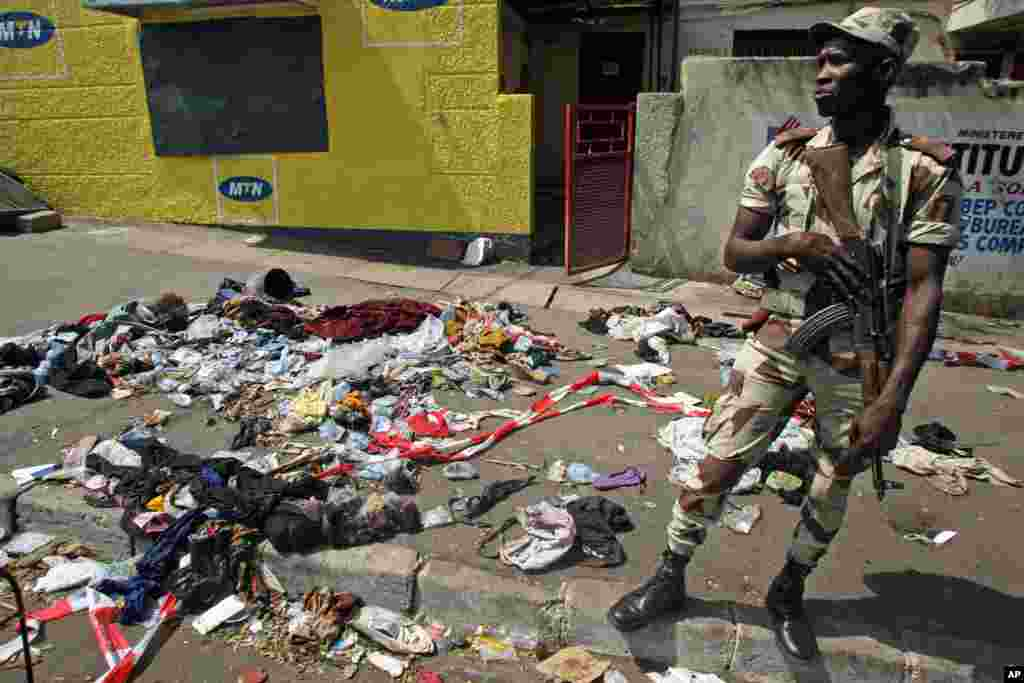 A soldier stands next to the belongings of people involved in a stampede in Abidjan, Ivory Coast, January 1, 2013.