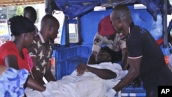 Rescue workers carry an injured person from a transport at St Gerard hospital in Kaduna, Nigeria, June 17, 2012.