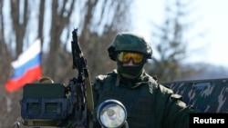 一名据信是俄军士兵的军人守卫在克里米亚首府辛菲罗波尔城外一处乌克兰军事驻地外。(2014年3月3日)
