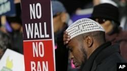 """Abdirahman """"OJ"""" Mohamed dari Seattle memegang poster bertuliskan """"Tidak Ada Dinding, Tidak Ada Larangan,"""" dalam unjuk rasa memprotes kebijakan pengetatan imigrasi, 6 Desember 2017, di luar pengadilan federal di Seattle."""