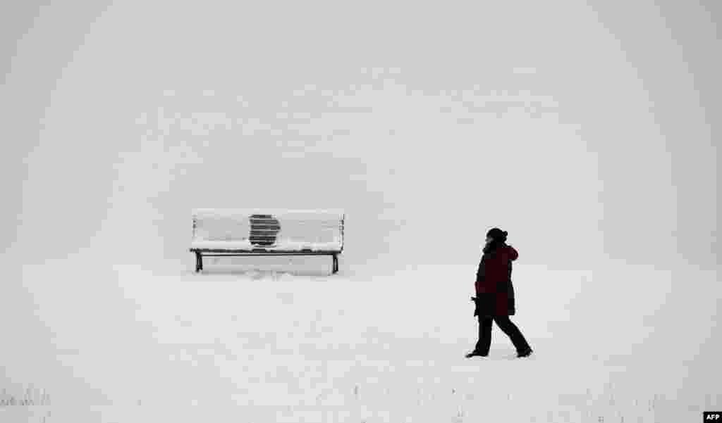 Seorang perempuan berjalan di sepanjang sungai Spree pada suatu hari musim dingin di Berlin, Jerman.