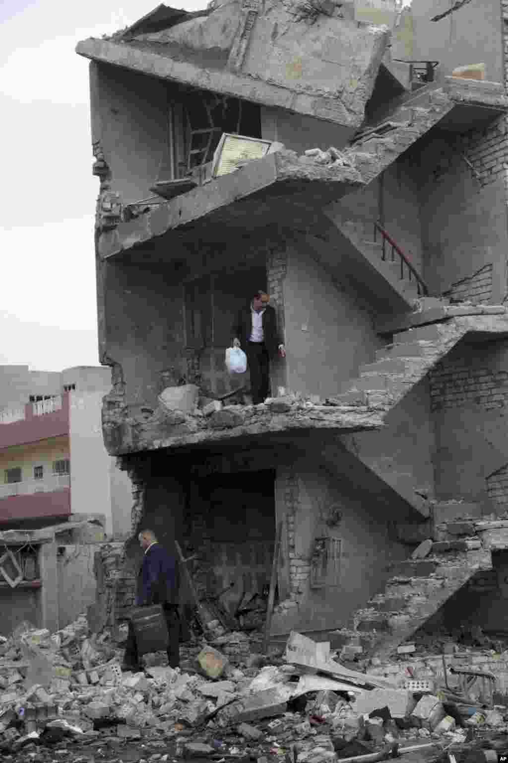 이라크 뉴바그다드의 상업지구에서 차량 폭탄 테러가 발생한 가운데, 주민들이 폭발로 심하게 부서진 건물에서 자신들의 물건을 챙기고 있다.