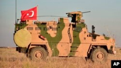 FILE - A Turkish military vehicle is seen on the outskirts of the Syrian town of Manbij, Nov. 1, 2018.