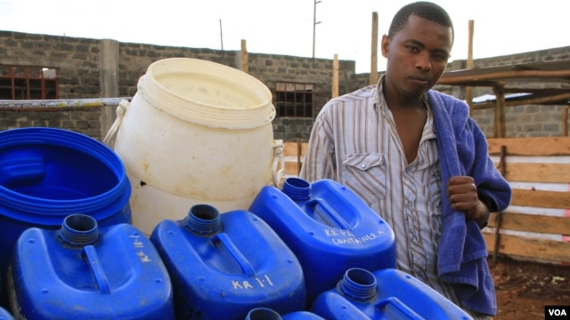 Fresh Life Frontline member Bernard Mutuku stands next to waste collection containers at the processing facility in the industrial area of Nairobi, Kenya, September 11, 2012. (J. Craig/VOA)