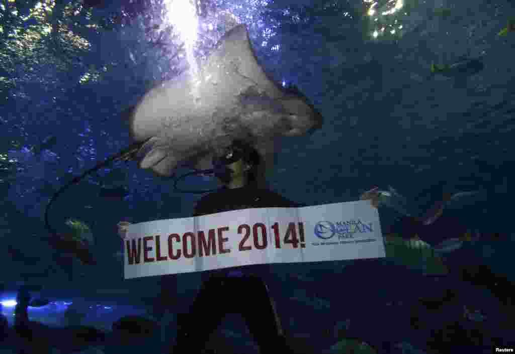 필리핀 마닐라 해양공원에서 잠수부가 2014년 새해를 환영하는 문구를 펼쳐보이고 있다.