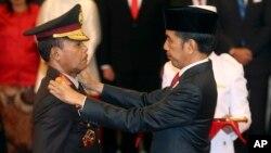 Kepala Kepolisian Republik Indonesia Baru Jenderal Idham Aziz (kiri), menerima lencana baru dari Presiden Indonesia Joko Widodo (kanan), dalam upacara pengambilan sumpah jabatan di Istana Negara, Jakarta, Jumat, 1 November 2019. (AP Foto / Achmad Ibrahim)