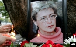 FILE - People light candles next to a portrait of Russian journalist Anna Politkovskaya during a rally in St. Petersburg in 2006.