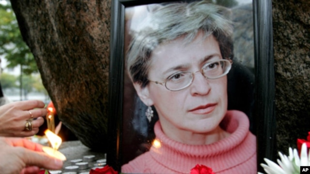 People light candles next to a portrait of Russian journalist Anna Politkovskaya during a rally in St. Petersburg (File 2006)