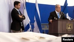 Israel's PM Benjamin Netanyahu (R) delivers a speech near the covered bodies of victims of Friday's attack on a Paris grocery, during their joint funeral in Jerusalem, Jan. 13, 2015.