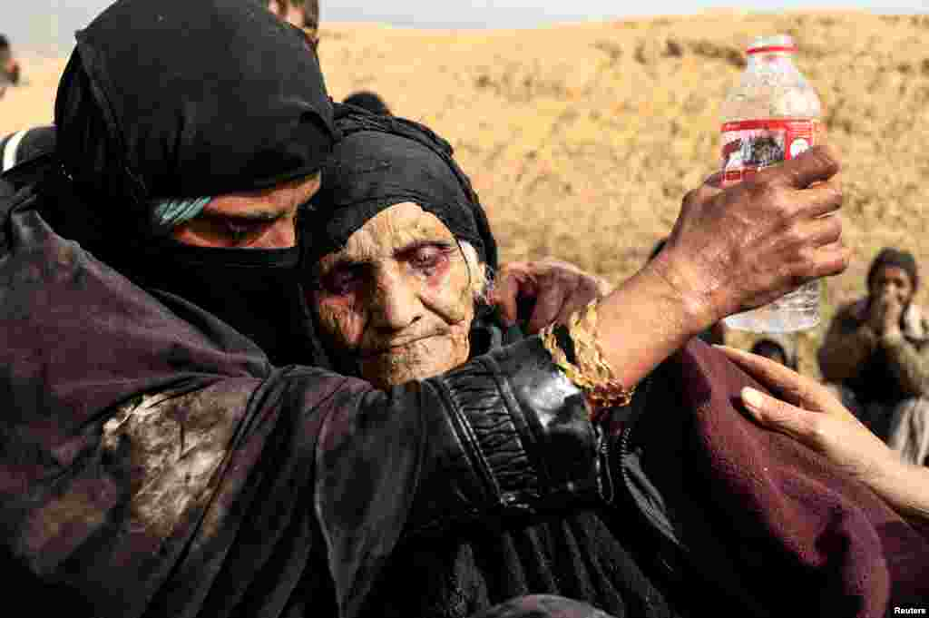 Displaced Iraqi women who just fled their home, rest in the desert as they wait to be transported while Iraqi forces battle with Islamic State militants in western Mosul.
