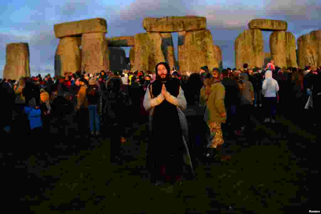 Revelers enjoy the sunrise as they welcome the winter solstice at Stonehenge stone circle in Amesbury, Britain.