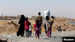 FILE - A displaced family from the minority Yazidi sect walks towards the entrance of Mosul, Aug. 21, 2014.