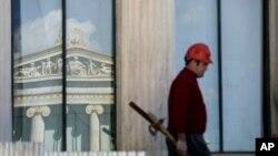 Seorang pekerja konstruksi di atas gedung Athens Academy abad 19 di Athena, Yunani (3/3).