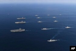 Three U.S. aircraft carriers USS Nimitz, left top, USS Ronald Reagan, left center, and USS Theodore Roosevelt, left bottom, participate with other U.S. and South Korean navy ships during the joint naval exercises between the United States and South Korea