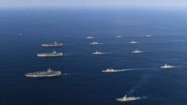 Three U.S. aircraft carriers USS Nimitz, left top, USS Ronald Reagan, left center, and USS Theodore Roosevelt, left bottom, participate with other U.S. and South Korean navy ships during the joint naval exercises between the United States and South Korea.