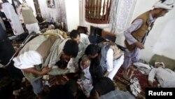 Warga menolong seorang pria yang terluka akibat bom bunuh diri di Sana'a, Yaman (20/3).