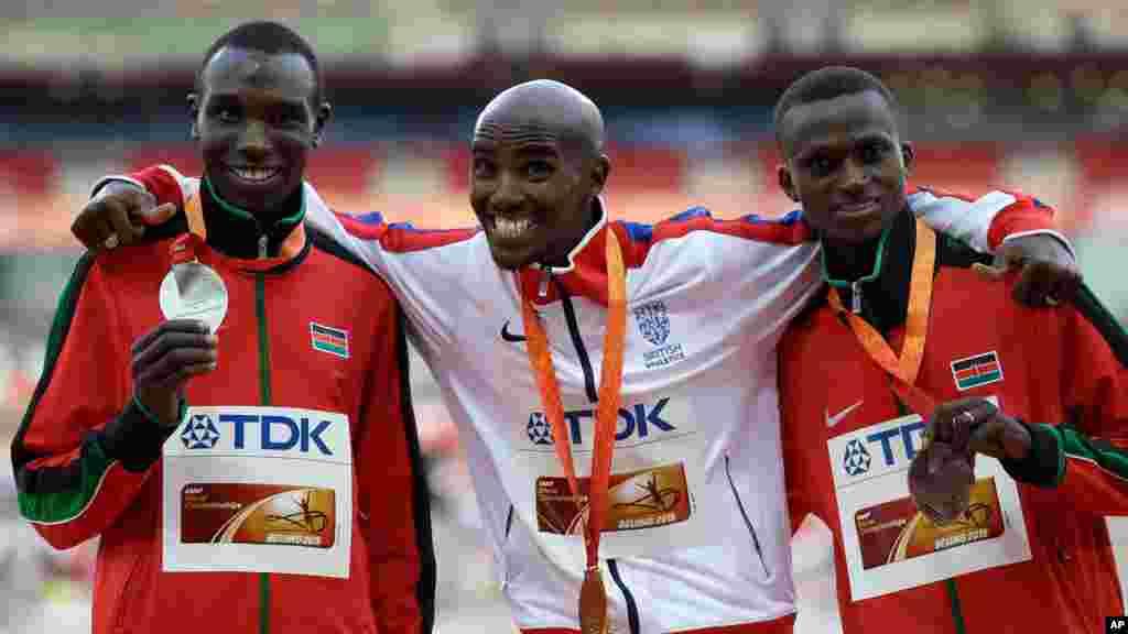 Mo Farah de la Grande-Bretagne, centre, médaille d'or au cou, pose avec Geoffrey Kipsang Kamworor du Kenya, à gauche, et Paul Kipngetich Tanui du Kenya sur le podium de la 10000m masculin aux championnats du monde d'athlétisme au stade Nid d'oiseau à Pékin, d23 août , 2015.