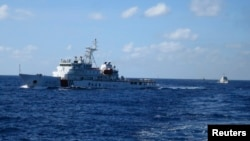 FILE - Chinese ships chase Vietnamese vessels, not shown, after they came within 10 nautical miles of a Chinese oil rig in the South China Sea, July 15, 2014.