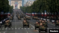 Armored army vehicles descend from the Champs Elysees during the traditional Bastille Day military parade in Paris, France, July 14, 2013.