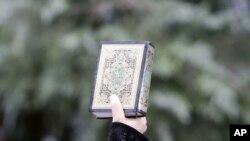 ພວກປະທ້ວງຄົນນຶ່ງຍົກປຶ້ມຄໍາພີ Koran ຂຶ້ນໃນລະຫວ່າງການປະທ້ວງຕໍ່ຕ້ານລັດຖະບານ ປ. Bashar al-Assad ຢູ່ນອກສະຖານກົງສູນຂອງຊີເຣຍ ທີ່ກຸງ Istanbul, ວັນທີ 3 ສິງຫາ 2011.