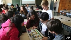 FILE - Students look at a World Cup sticker book during their Portuguese class, in Sao Paulo, Brazil, May 21, 2018.