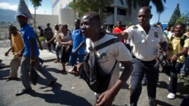 A demonstrator who began to break car windows, is detained by police during a protest against the proposed wage increase garment workers say is too little, at an industrial park in Port-au-Prince, Haiti, Dec. 11, 2013.