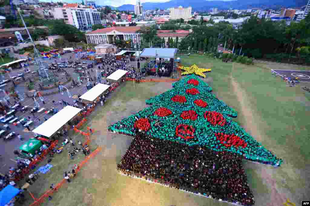 This picture, released by the Honduran presidency, shows the biggest human Christmas tree, which set a new Guinness World Record, at the Plaza La Democracia, in Tegucigalpa, Honduras.
