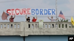FILE - Demonstrators with signs on an overpass in Indianapolis, Indiana, protest against people who immigrate illegally.