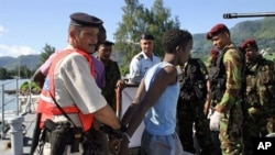 One of the arrested Somali pirates is handcuffed by police upon his arrival in the Port Victoria with the six Seychellois fishermen, 31 Mar 2010