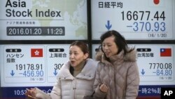 Woman walk past an electronic stock board showing Japan's Nikkei 225, top right, and Hong Kong's Hang Seng, bottom left, at a securities firm in Tokyo, Jan. 20, 2016.