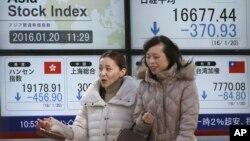 在东京一家证券公司,妇女走过显示亚洲各地股市行情的电子屏幕(2016年1月20日)