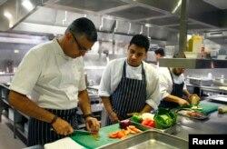 Chef Atul Kochhar (L) slices tomatoes at his Benares restaurant in Mayfair, central London, Jan. 21, 2015.