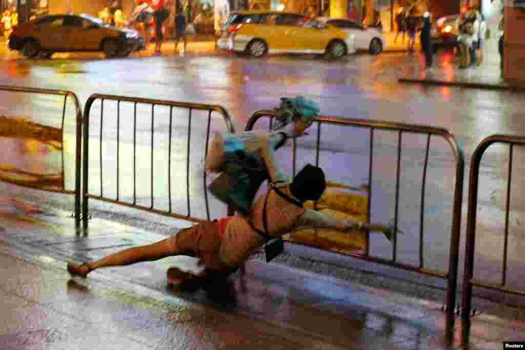 Seorang perempuat terjatuh di trotoar saat angin topan Nesat melanda Taipei, Taiwan.