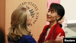 U.S. Secretary of State Hillary Clinton (L) introduces Burma's opposition leader Aung San Suu Kyi to speak at the United States Institute of Peace in Washington, D.C., September 18, 2012.