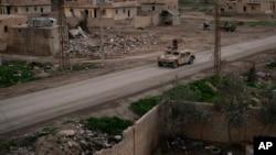"""Vozilo """"humvee"""" vozi kroz selo koje su od militanata Islamske države nedavno zauzeli borci Sirijskih demokratskih snaga, koje uživaju podršku SAD, u blizini Boguza, Sirija, 17. februara 2019."""