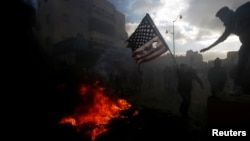 A Palestinian protester prepares to burn a U.S. flag during clashes with Israeli troops at a protest against U.S. President Donald Trump's decision to recognize Jerusalem as the capital of Israel, near the Jewish settlement of Beit El, near the West Bank city of Ramallah Dec. 7, 2017.