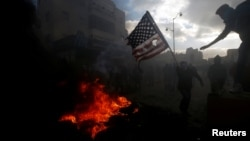 A Palestinian protester prepares to burn a U.S. flag during clashes with Israeli troops at a protest against U.S. President Donald Trump's decision to recognize Jerusalem as the capital of Israel, near the Jewish settlement of Beit El, near the West Bank
