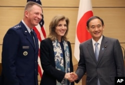 FILE - U.S. Ambassador to Japan Caroline Kennedy, center, accompanied by Lt. Gen. John Dolan, left, commander of U.S. Forces Japan, shakes hands with Japanese Chief Cabinet Secretary Yoshihide Suga after their joint press conference in Tokyo.