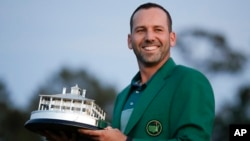 Spain's Sergio Garcia holds the first-place trophy while wearing the winner's green jacket after taking after Masters' title in a playoff, April 9, 2017, in Augusta, Georgia. (AP Photo/David Goldman)