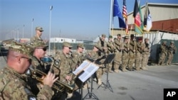The International Security Assistance Forces band plays during flag-lowering ceremony in Kabul as NATO forces ceremonially end their 13 year combat mission in Afghanistan, Dec. 8, 2014.
