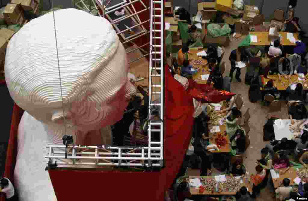 A worker puts the finishing touches to a five-meter (16-feet) tall bust of the late Hong Kong singer and actor Leslie Cheung as origami cranes, folded by fans from around the world in their attempt to set a Guinness world record for the largest number of origami cranes exhibited, are counted at a shopping mall in Hong Kong.