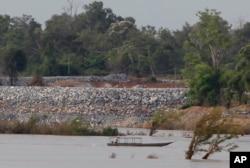 FILE - A fishing boat passes near a construction site of a dam, near Cambodia-Laos borders, in Preah Romkel village, Stung Treng province, northeast of Phnom Penh, Cambodia, June 20, 2016.