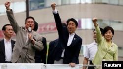 PM Jepang Minister Shinzo Abe (tengah), yang juga merupakan pemimpin partai Liberal Demokratik berkuasa, mengepalkan tangannya untuk memberi semangat kepada para pendukungnya dalam kampanye parlemen di Tokyo, 4 Juli 2013 (Foto: dok).