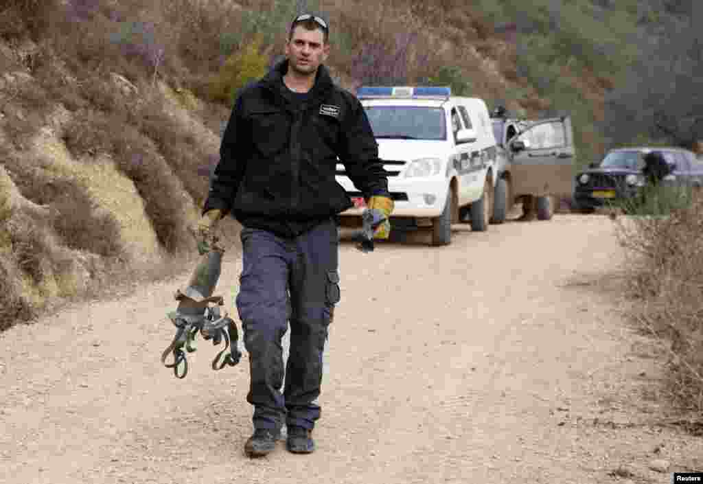 An Israeli police explosive expert carries the remains of a rocket after it landed near the northern town of Kiryat Shmona, Israel, Dec. 29, 2013.