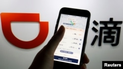 FILE - The app of Chinese ride-hailing giant Didi is seen on a mobile phone in front of the company logo displayed in this illustration picture taken July 1, 2021. (REUTERS/Florence Lo/Illustration/File Photo)